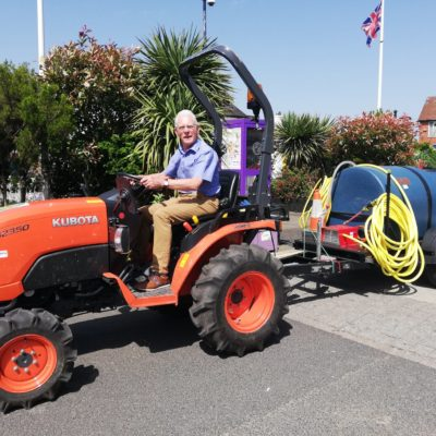 Mayor On Town Council Tractor Watering Plants - Click to open full size image